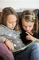 sister - Siblings using digital tablet together on sofa Stock Photo - Premium Royalty-Freenull, Code: 698-07611740
