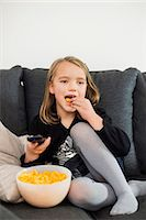 Girl eating snacks while watching TV on sofa at home Stock Photo - Premium Royalty-Freenull, Code: 698-07611744