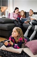 Girl watching TV on floor with family in background Stock Photo - Premium Royalty-Freenull, Code: 698-07611753