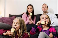 families eating ice cream - Family eating ice cream in living room Stock Photo - Pre
