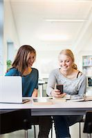 Happy teenage girls using mobile phone at table in school library Stock Photo - Premium Royalty-Freenull, Code: 698-07611777