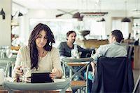 Businesswoman using digital tablet in restaurant Stock Photo - Premium Royalty-Freenull, Code: 698-07611878