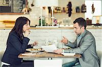 Side view of businessman with female colleague discussing paperwork at restaurant table Stock Photo - Premium Royalty-Freenull, Code: 698-07611882