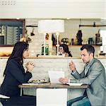 Side view of businessman with female colleague discussing at restaurant table
