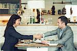 Side view of businessman and businesswoman shaking hands at restaurant table