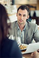 Businessman discussing with female colleague at restaurant table Stock Photo - Premium Royalty-Freenull, Code: 698-07611885