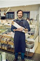 Portrait of mature male baker holding loaves of bread in supermarket Stock Photo - Premium Royalty-Freenull, Code: 698-07611899
