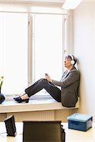 Full length of businesswoman listening music while sitting on window sill Stock Photo - Premium Royalty-Freenull, Code: 698-07611942