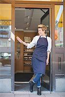 small business owners - Full length of happy female owner gesturing while standing at cafe entrance Stock Photo - Premium Royalty-Freenull, Code: 698-07611979