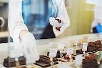 Midsection of female worker packing sweet food at display cabinet in cafe Stock Photo - Premium Royalty-Freenull, Code: 698-07611980