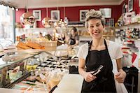 small business owners - Portrait of happy saleswoman cutting cheese at counter in supermarket Stock Photo - Premium Royalty-Freenull, Code: 698-07611996