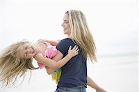 Mother swinging daughter over water at beach Stock Photo - Premium Royalty-Free, Artist: ableimages, Code: 618-07612114