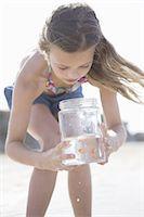 Girl looking at jar on beach Stock Photo - Premium Royalty-Freenull, Code: 618-07612169