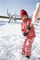 Girl holding snow shovel of snow Stock Photo - Premium Royalty-Free, Artist: Ikon Images, Code: 618-07612288