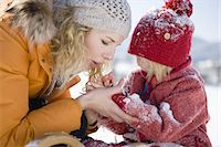Mother blowing snow from daughters hands Stock Photo - Premium Royalty-Freenull, Code: 618-07612297