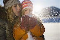Mother and girl blowing snow Stock Photo - Premium Royalty-Freenull, Code: 618-07612302