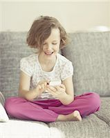 Young girl using cellphone on sofa Stock Photo - Premium Royalty-Freenull, Code: 618-07612337