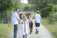 Family walking along country path with cattle Stock Photo - Premium Royalty-Freenull, Code: 618-07612467