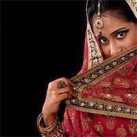 Portrait of beautiful mystery young Indian woman covering her face by veil, looking at camera, copy space at side, isolated on black background. Stock Photo - Royalty-Freenull, Code: 400-07616579