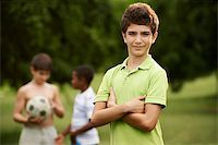 diego_cervo (artist) - Portrait of elementary age kid looking at camera with arms crossed and children playing soccer in background Stock Photo - Royalty-Free, Artist: diego_cervo, Code: 400-07632551