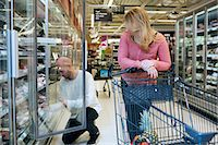 Mid adult couple buying groceries in supermarket Stock Photo - Premium Royalty-Freenull, Code: 698-07635220