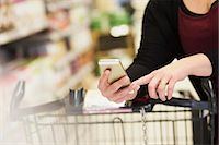 Midsection of woman checking shopping list in supermarket Stock Photo - Premium Royalty-Freenull, Code: 698-07635226