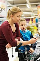 Mother and son checking shopping list in grocery store Stock Photo - Premium Royalty-Freenull, Code: 698-07635235