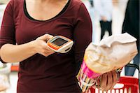 Midsection of woman scanning product with bar code reader in supermarket Stock Photo - Premium Royalty-Freenull, Code: 698-07635238