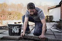 Carpenter positioning stone tile in yard Stock Photo - Premium Royalty-Freenull, Code: 698-07635274