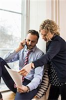 partnership - Businessman answering smart phone while discussing over document with female colleague by office window Stock Photo - Premium Royalty-Freenull, Code: 698-07635279