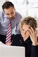 Senior businesspeople looking at laptop in office Stock Photo - Premium Royalty-Freenull, Code: 698-07635280