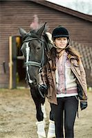 equestrian - Young woman with horse walking outside barn Stock Photo - Premium Royalty-Freenull, Code: 698-07635319