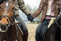 Low section of couple holding hands while riding horses Stock Photo - Premium Royalty-Freenull, Code: 698-07635322