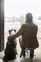 Full length rear view of young woman arm around dog in doorway of horse stable Stock Photo - Premium Royalty-Freenull, Code: 698-07635334