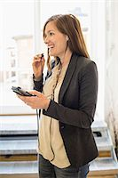 Smiling businesswoman listening to music through mobile phone in office Stock Photo - Premium Royalty-Freenull, Code: 698-07635340