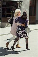 Full length rear view happy senior women walking on street Stock Photo - Premium Royalty-Freenull, Code: 698-07635390