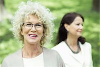 Portrait of smiling senior woman at park with friend in background Stock Photo - Premium Royalty-Freenull, Code: 698-07635418