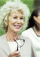 Happy senior woman looking away while holding glasses in park Stock Photo - Premium Royalty-Freenull, Code: 698-07635420