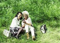 Full length of senior women using mobile phone on grass Stock Photo - Premium Royalty-Freenull, Code: 698-07635426