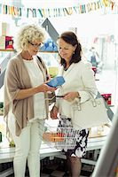 Senior female friends shopping in store Stock Photo - Premium Royalty-Freenull, Code: 698-07635430