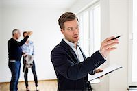 person holding sign - Real estate agent examining house with couple discussing in background Stock Photo - Premium Royalty-Freenull, Code: 698-07635454
