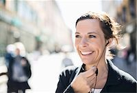 Smiling mature businesswoman talking through headphones on city street Stock Photo - Premium Royalty-Freenull, Code: 698-07635491