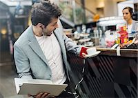 Panic mid adult man holding laptop and coffee at cafe Stock Photo - Premium Royalty-Freenull, Code: 698-07635516