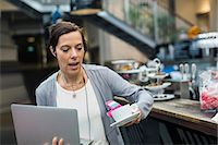 people in panic - Panic mature woman holding laptop and coffee at cafe Stock Photo - Premium Royalty-Freenull, Code: 698-07635518