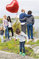 different - Boy holding balloon on rock with homosexual families in background Stock Photo - Premium Royalty-Freenull, Code: 698-07635522