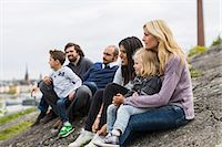 Homosexual families relaxing on rock at lakeshore Stock Photo - Premium Royalty-Freenull, Code: 698-07635524