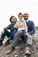 stockholm - Portrait of happy male homosexual family relaxing on rock Stock Photo - Premium Royalty-Freenull, Code: 698-07635526