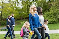 Female homosexual family walking at park with gay couple in background Stock Photo - Premium Royalty-Freenull, Code: 698-07635531