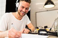 Happy young businessman wearing headphones while writing in book at creative office Stock Photo - Premium Royalty-Freenull, Code: 698-07635558