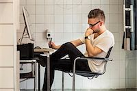 small business owners - Side view of young businessman at computer desk in new office Stock Photo - Premium Royalty-Freenull, Code: 698-07635586
